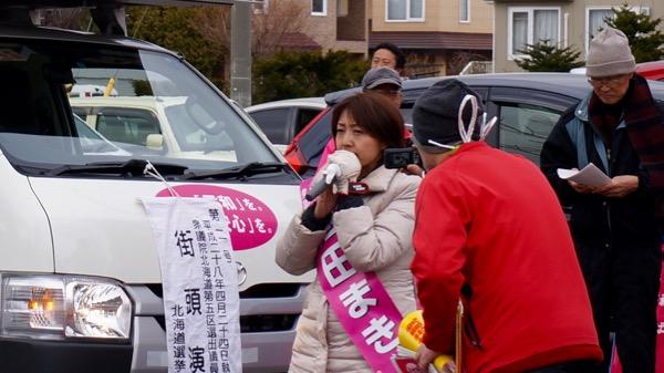 街頭演説する池田真紀候補の横を写真を撮りながら通る支持者