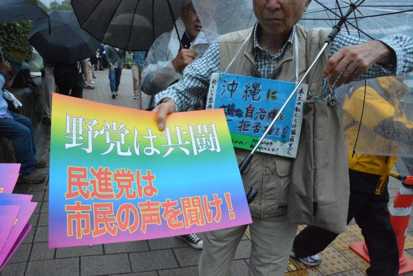 集会参加者は「民進党は市民の声を聞け」のプラカードを次々と受け取って行った。=19日、国会正門につながる歩道の入り口 撮影:筆者=