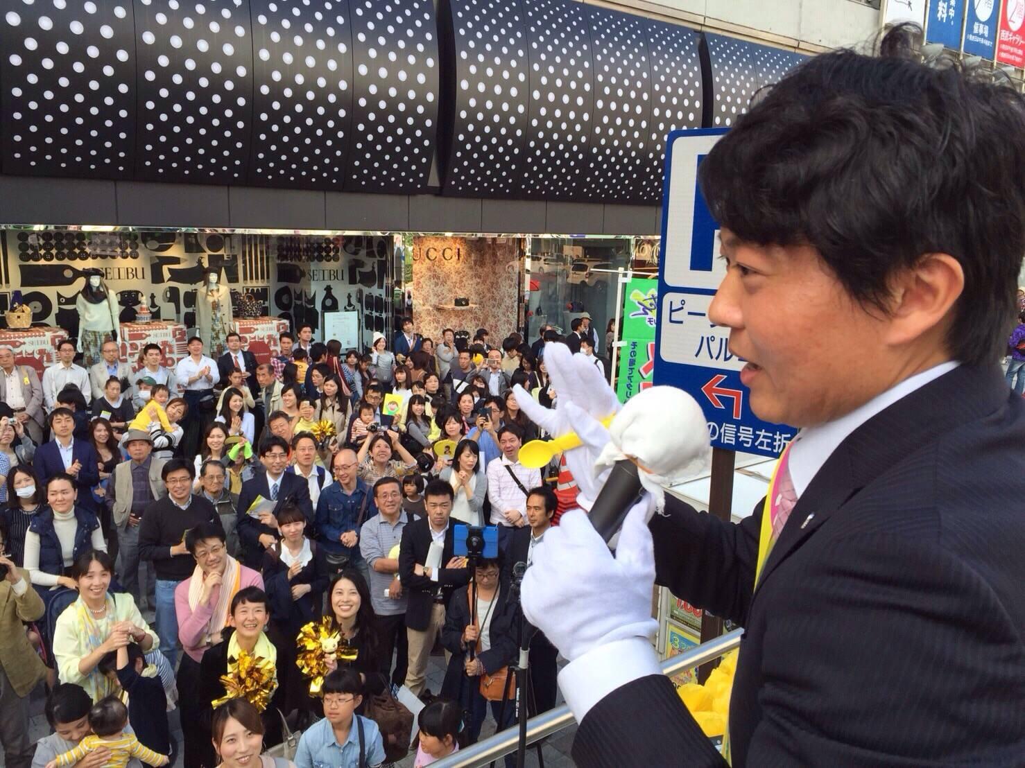 吉井氏の演説の風景。右手にはなぜか黄色いスプーンを持っている